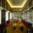 fotografia da biblioteca da ajuda sala com mesas e cadeiras, e com muitas estantes de livros