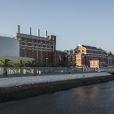 fotografia do edificio completo do museu da eletricidade, com parte do jardim que antecede o museu e o rio tejo.